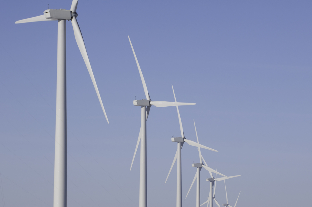 Tops of wind turbines against a wintry blue sky in northern Illinois